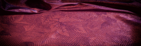 Texture, background, pattern. fabric silk dark maroon. Silk organza mood, but with a beautiful satin face. This fabric has a crunchy drape of organza, but one face is a brilliant satin. Stock Photo