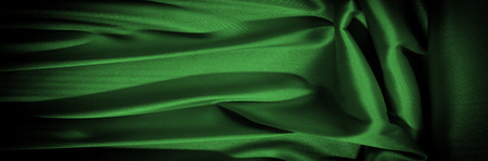 Texture, background, pattern. Fabric silk is dark green. Expressing harmony, global appeal, The combination of green and black, color purple contains passion, strength and energy. Green color,
