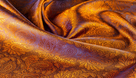 Silk. Lining brown. Closeup of lines in brown silk fabric. Brown background with shadows and smooth lines. brown background of shiny satin or silk folds