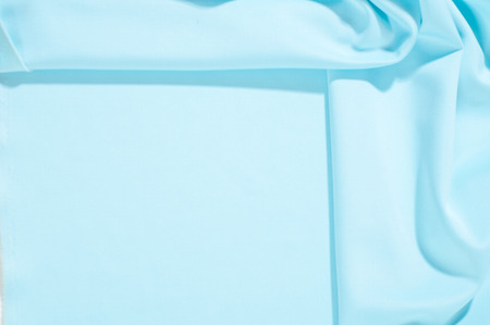Texture. Background. Template. Pamper your design with a luxurious light blue silk flag. The blue dip can boast of a dull sheen and a crisp hand. His stiff drape creates volume when he falls. 免版税图像 - 120218811