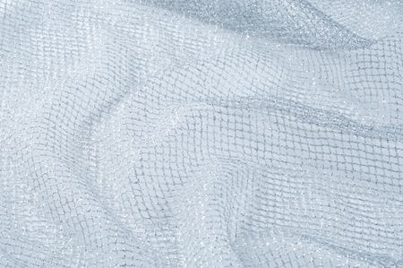 fabric, background texture. White silver mesh fabric, with a woven metallic thread. Silver fashion mesh! Flickering beads add texture and shine to the piece. Фото со стока