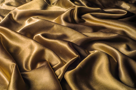 Fabric made of silk fabric metal thread metallic sheen gold. Just like looking at a stunning waterfall, this golden yellow Silk Charmeuse stands alone. Luminous and light-flowing steel metallic color Imagens