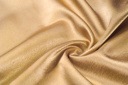 Fabric made of silk fabric metal thread metallic sheen gold. Just like looking at a stunning waterfall, this golden yellow Silk Charmeuse stands alone. Luminous and light-flowing steel metallic color Stock fotó