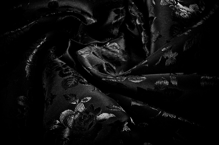 fabric, background texture. silk black fabric with a pattern of flowers. Get lost in the beautiful illustrated floral print in this black and white silk frame.
