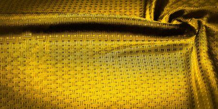 Texture de fond, motif. Tissu en soie jaune moutarde avec un petit motif à carreaux. Jaune étouffé tressé avec des sous-titres avec des étincelles - un design graphique brillant. Pièces individuelles.