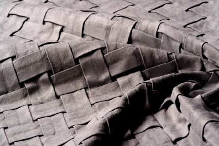 Textured, background, pattern, Woven fabric of intertwined folded strips of gray. Fashionable interior design, web pages, and other.