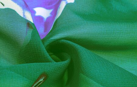 Texture, background, green silk fabric with a blue floral print.