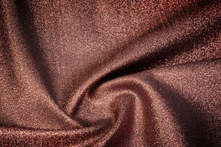 Texture, background, pattern. Cloth with burgundy coating with metallic gold thread.
