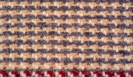 Background texture, pattern. The fabric is thick, warm in a cage, beige.
