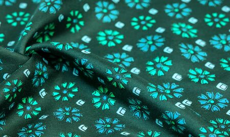 silk fabric of green color with blue and white flowers, dense fabric, bilateral on the basis of triacetate fibers. Texture, Background, Pattern, Decor, Modern, Textile, Art, Design, Banque d'images - 130127370