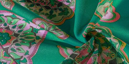 texture, background, multicolored silk fabric with a pattern of patterns on a green background, jacquard pattern