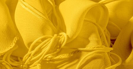 The background, pattern, texture, wallpaper, yellow pale silk fabric has a brilliant shine.