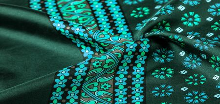 silk fabric of green color with blue and white flowers, dense fabric, bilateral on the basis of triacetate fibers.