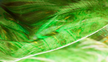 Background texture, pattern. Silk from a greenish emerald shade.