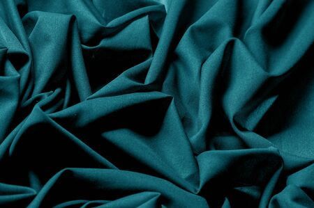 Textured, background, pattern, turquoise fabric. This is an unusual fabric that has an elegant appearance with a rich and coarse texture. It is tightly knit with designs built into the fabric itself