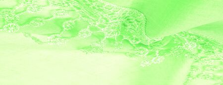Texture, background, pattern, postcard, silk fabric, female spring green scarf with lace wrappers. Use these fancy images to create your print and digital materials. Foto de archivo - 129943704
