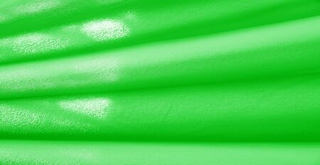 Picture. Texture, background. green emerald silk fabric. This medium  silky silk fabric has a wonderful shine with slight color variations to give the look a strip in the fabric.
