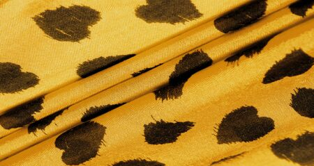Texture, background, pattern, postcard, silk fabric, yellow print from the fabric of black hearts, your projects will not go unnoticed, this fabric will help you with this Stock Photo