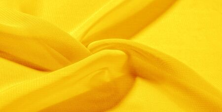 texture background pattern yellow silk fabric. This silk organza has a gentle open weave. Use this luxurious fabric for anything from your design for special occasions to creating your projects.