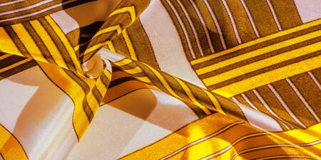 Texture, background, silk fabric with a yellow striped pattern. The design of this fabric is dedicated to a white rabbit mosaic representing the look of a fabulous vest. Imagens