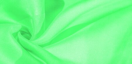 Texture, background, pattern, silk fabric of green color. This silk is incredibly exquisite. Projects made from this will last a long time and will still be in fairly good condition. Stockfoto - 131276160