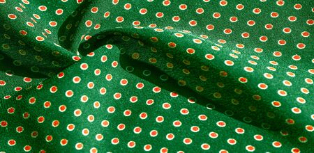Texture background, pattern,  green silk fabric with red polka dots. Light and silky-soft satin pendant is perfect for your design, online projects. It is also perfect for screensavers and wallpapers Stockfoto - 131276391