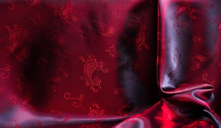 Texture, fabric, red silk with paisley pattern. This beautiful printed silk Charmeuse has a bold paisley pattern. In the patriotic appearance there are colors red, The fabric has a slippery hand