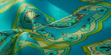 texture, background, multicolored silk fabric with a pattern of patterns on a turquoise background,