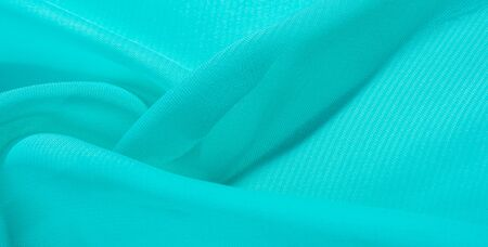 texture background pattern blue silk fabric. this silk organza has a delicate open weave Use this luxurious fabric for anything from your design for special occasions to the creation of your projects
