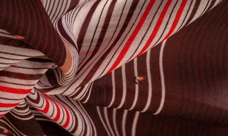 Texture, pattern, collection, silk fabric, brown background with a striped pattern of white and red lines, the Spanish theme, which is great for the design of procedures and projects.