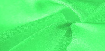 Texture, background, pattern, silk fabric of green color. This silk is incredibly exquisite. Projects made from this will last a long time and will still be in fairly good condition.
