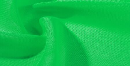 texture background pattern green silk fabric. This silk organza has a gentle open weave. Use this luxurious fabric for anything from your design for special occasions to creating your projects.