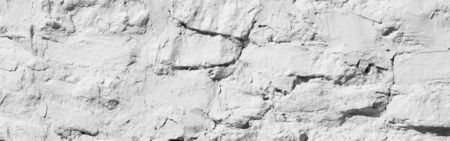 Texture background, pattern. The wall is lined with granite stones and whitewashed with lime. a continuous vertical brick or stone structure that encloses or divides an area of land.