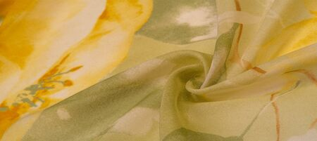 Texture, background, thin translucent silk with a large pattern. On a yellow background - lettuce and orange flowers, each with its own pattern, which makes the overall composition a bit abstract. Zdjęcie Seryjne