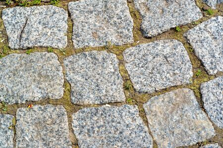 Granite pavement, roadway, road, paving, causeway, pave. a very hard, granular, crystalline, igneous rock composed of quartz, mica, and feldspar and often used as a building stone. Stock Photo