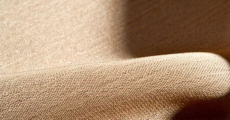 Background, pattern, texture, beige golden silk fabric It has a smooth matte finish and is durable due to a slightly twisted yarn. Use this luxurious fabric for anything - from design to your projects Stock fotó - 138616885