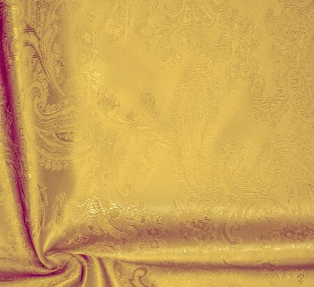 Texture, background, The silk fabric is yellow. This yellow stamping silk crepe de China is here to charge your design! Live combination of floral and paisley diagonal stripes on a greasy background Stock Photo