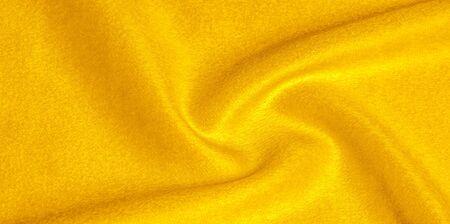 patrón, textura, fondo, lana cálida, tela amarilla. Acerca de Esta tela es bastante fina. Tiene una variedad de hilos con variaciones de color muy pequeñas para una apariencia final clara con un brillo sutil. Foto de archivo