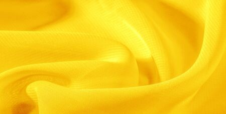 texture background pattern yellow silk fabric. This silk organza has a gentle open weave. Use this luxurious fabric for anything from your design for special occasions to creating your projects. Zdjęcie Seryjne - 138633273