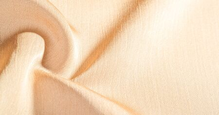 Background, pattern, texture, beige golden silk fabric It has a smooth matte finish and is durable due to a slightly twisted yarn. Use this luxurious fabric for anything - from design to your projects Stock fotó