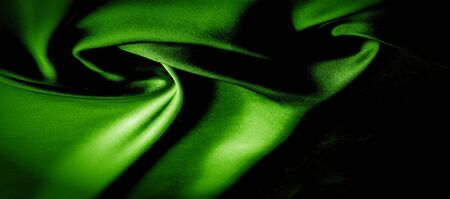 texture, background, pattern. green silk fabric panoramic photo. Silk Duke mood Satin is a beautiful and royal silk fabric. It has a shimmering shine,