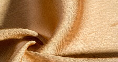 Background, pattern, texture, beige golden silk fabric It has a smooth matte finish and is durable due to a slightly twisted yarn. Use this luxurious fabric for anything - from design to your projects