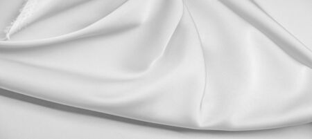 background texture, pattern. White silk fabric. It has a smooth matte finish and gets its strength from slightly twisted yarns. use this luxurious fabric for anything