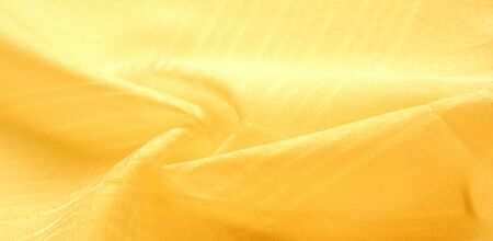texture background, pattern. silk yellow fabric. From Telio, this organza has a thin, open weave that is thicker and sharper than silk gauze. Use this luxurious fabric for anything. The possibilities are really endless! Imagens