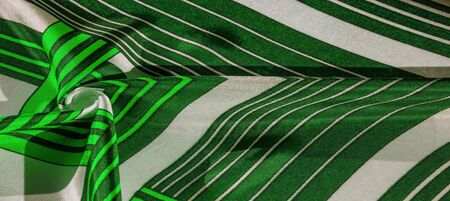 Texture,  silk fabric with a green striped pattern. The design of this fabric is devoted to a patchwork mosaic in the style of a white rabbit, representing what a fairytales vest might look like. Stockfoto