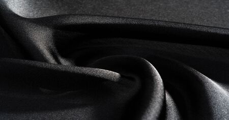 Background, pattern, texture, wallpaper, black silk fabric.  Add a touch of luxury to any design, putting it in this ultra-soft and very lightweight polyester lining fabric. Stock Photo