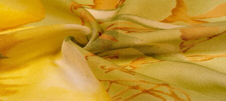 Texture, background, thin translucent silk with a large pattern. On a yellow background - lettuce and orange flowers, each with its own pattern, which makes the overall composition a bit abstract. Reklamní fotografie