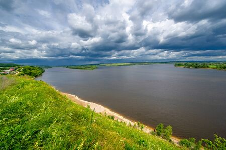 Summer landscape, a large full-flowing river, meadow flowers on the banks of the river, mighty clouds in the sky Stock fotó