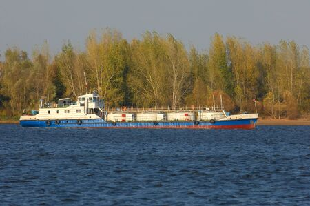 Autumn landscape, river, Works carried out on the river, riverboats, sunny day, wind raises the waves, dark lead color of water,