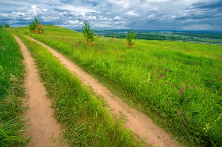 Summer landscape, a large full-flowing river, meadow flowers on the banks of the river, mighty clouds in the sky, a tourist walk along the Kama River